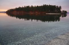Färger av gryning ger ett varmt glöd till en ö och dess reflexion i fjärden Royaltyfri Bild