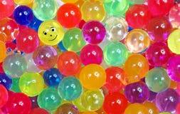 Färger av regnbågen Mångfärgad hydrogel klumpa ihop sig texturbakgrund Små färgrika pärlor Ordet FÄRG på kulöra räknare i skarp f royaltyfri bild