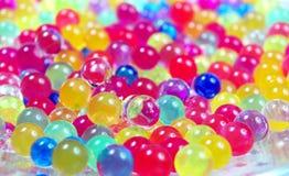 Färger av regnbågen Mångfärgad hydrogel klumpa ihop sig texturbakgrund Top beskådar Ordet FÄRG på kulöra räknare i skarp fokus mo royaltyfri fotografi