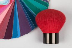 Färgfandäck med prövkopior av olika målarfärger med den röda borsten för makeup royaltyfria bilder