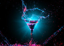 Färgglad coctail i exponeringsglas med färgstänk arkivfoton