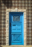 Färgglad dörr som omges av geometriska stenar Arkivbild