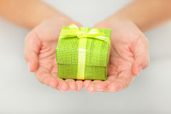 Färgglad grön gåva i kupade händer Royaltyfri Fotografi