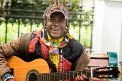 Färgglad kläder för gatakonstnär som sjunger med gitarren royaltyfria bilder