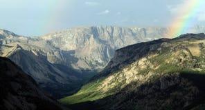 Färgglad regnbåge i ett bergigt landskap Arkivfoto