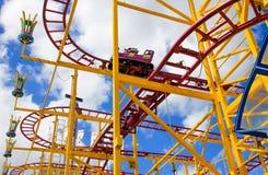 Färgglad rollercoaster med vagnen Arkivbild