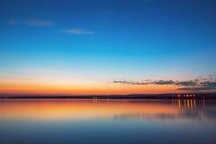 Färgglad solnedgång över sjön Arkivfoto