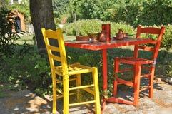 Färgglad tabell och stolar Arkivfoton