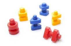 Färgglada toymuttrar - och - bultar Royaltyfri Foto