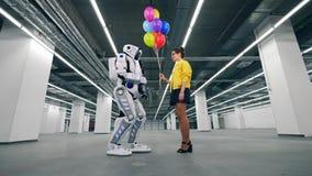Färgglade ballonger får erbjudna till en cyborg av en dam arkivfilmer