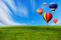 Färgglade ballonger för varm luft som flyger över grönt fält arkivbilder