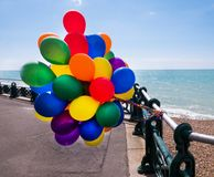 Färgglade ballonger, räcke, strand, blått hav och blå himmel Arkivbild