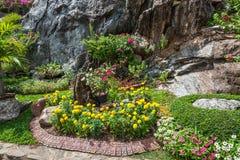 Färgglade blomsterrabatter och spolningsgräsbana Fotografering för Bildbyråer