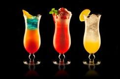Färgglade drinkar på svart bakgrund arkivfoton