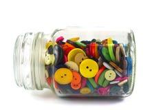 Färgglade herrekiperingsartiklarknappar i en glass krus Arkivbild
