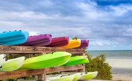 Färgglade kanoter på en tropisk strand arkivbild