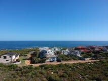 Färgglade kust- hem som är mörka - blått havvatten arkivfoton