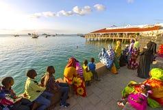 Färgglade kvinnor och ungar som håller ögonen på skepp på stranden i Zanziba royaltyfri fotografi