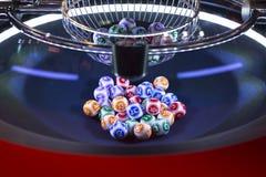 Färgglade lotteribollar i en maskin arkivfoton