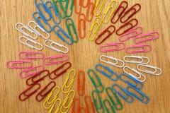 Färgglade Paperclips sänker lägger på stor cirkel för Wood offcentre textutrymme för bakgrund Royaltyfria Foton