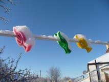 Färgglade plast- klädnypor som bakas ihop i snö Royaltyfria Foton