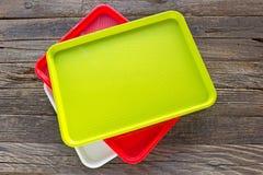 Färgglade plattor för mat för formell lunchplast-fyrkant på träbackgrou royaltyfri foto