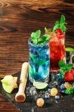 Färgglade söta coctailar med mintkaramellen, limefrukt, is, bär på träbakgrunden Uppfriskande sommardrycker kopiera avstånd Arkivbild