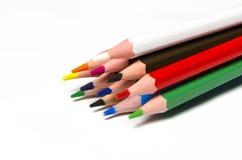 Färgglade skarpa blyertspennor ligger på bakgrund arkivfoton