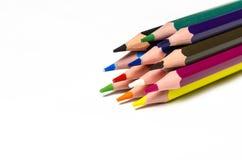Färgglade skarpa blyertspennor ligger på en vit bakgrund royaltyfri bild