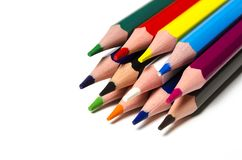 Färgglade skarpa blyertspennor ligger på en vit bakgrund arkivfoto