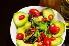 Färgglade sunda foods avokado, Olive Oil, äppelcidervinäger, Cherry Tomatoes, röda chili grönsallat, för sund matvana arkivfoton