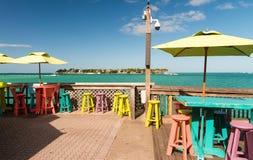 Färgglade tabeller och stolar på en terrass längs havet, holida Royaltyfri Fotografi