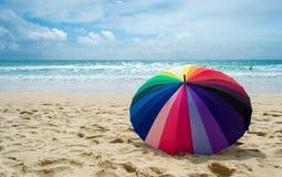 Färgglat paraply på stranden arkivfoto