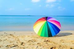 Färgglat paraply på stranden Royaltyfri Bild