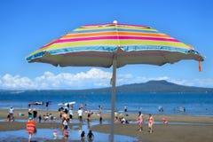 Färgglat strandparaply på en solig dag för sommar Arkivfoto