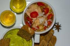Färgglat sunt foodsavokadodopp, brunt rostat bröd med organiska Olive Oil, med tonfisk för royaltyfri foto