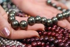 färghand som rymmer många pärlor Royaltyfri Foto