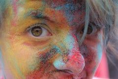 Färgkörningsgyckel, en ung flicka med hennes framsida som täckas i färg arkivfoton