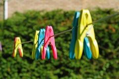 Färgklädnypor på washline Arkivfoto