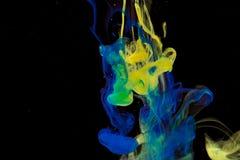 Färgmålarfärgdroppar i vatten Virvla runt för FÄRGPULVER som är undervattens- Arkivbild