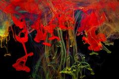 Färgmålarfärgdroppar i vatten Virvla runt för FÄRGPULVER som är undervattens- Arkivfoto