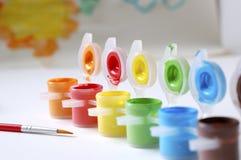 Färgmålarfärger och målarfärgborste Arkivbild