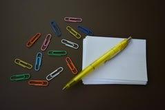 Färgpaperclips av olika färger med ark av vitbok för att anteckna och en gul penna på en brun matte bakgrund royaltyfria bilder