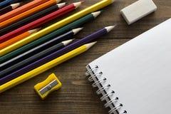 Färgpennor, anteckningsbok, radergummi och vässare Arkivbild