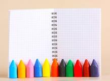 Färgpennor av olika färger står på bakgrunden av en anteckningsbok i en bur Arkivbild