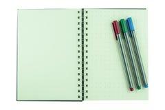 Färgpennor på den isolerade anteckningsboken arkivfoto
