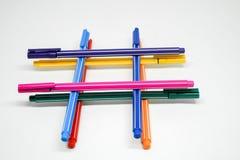 Färgpennor som tillsammans staplas Arkivbild