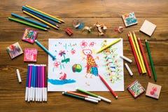 Färgpennor, tuschpennor och en teckning för barn` s Royaltyfri Foto