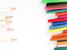 Färgpennor uppställda med vita blyertspennor Arkivbilder