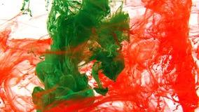 Färgpulver som virvlar runt i vatten, färgdroppe i vatten som fotograferas i rörelse arkivbilder